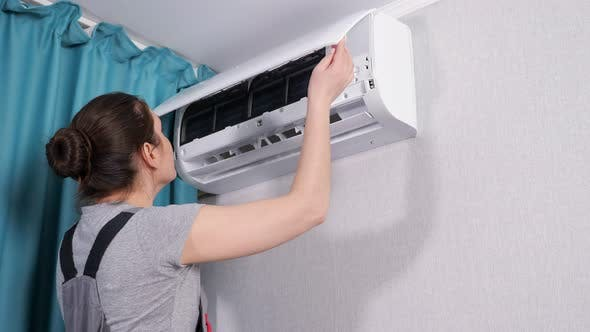 Apartment Owner with Screwdriver Opens Air Conditioner Lid