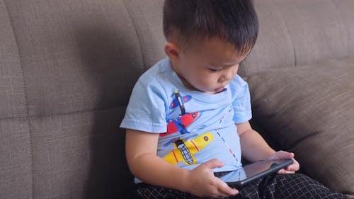 Little Boy Playing Smartphone On Sofa