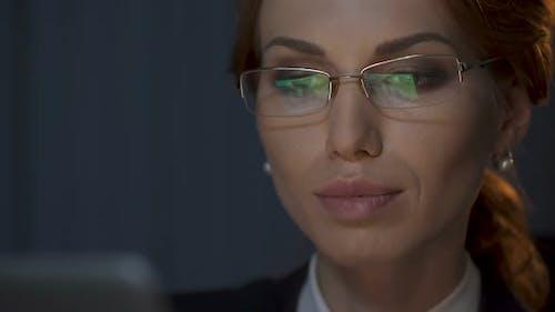 Geschäftsfrau Abnehmen Ihre Brille und Blick sorgfältig auf Laptop-Bildschirm