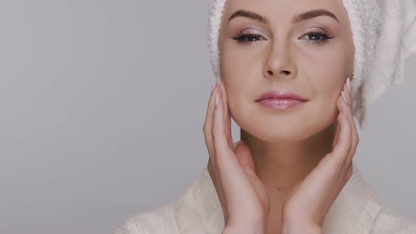 Thumbnail for Fresh and Young Woman Applying Cream on Face in Head Towel