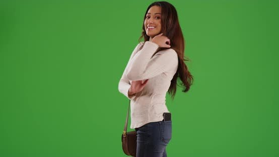Thumbnail for Hispanic woman with arms crossed, smiling at camera on green screen