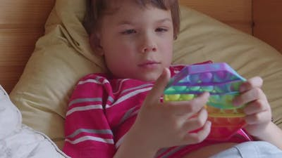 Toddler Kid Playing with the Pop It Toy Fidget