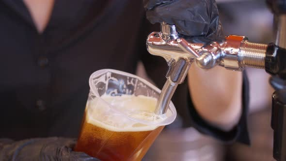 Thumbnail for Bartender Pouring Beer Into Glass with Bubbles Close Up