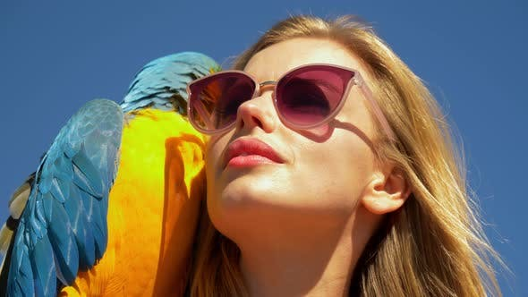Thumbnail for Blonde Model Wearing Pink Tinted Sunglasses on a Sunny Day with Parrot on Her Side