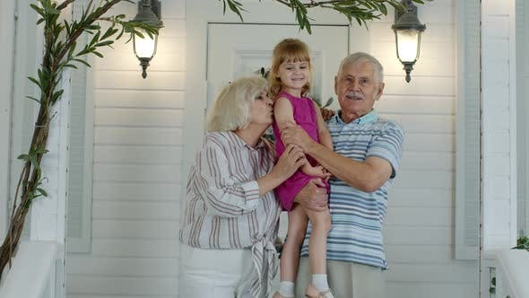 Thumbnail for Happy Senior Grandfather and Grandmother Couple Holding Granddaughter in Hands in Porch at Home