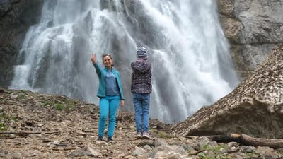 Girl Taking Photos of Mother Near Waterfall