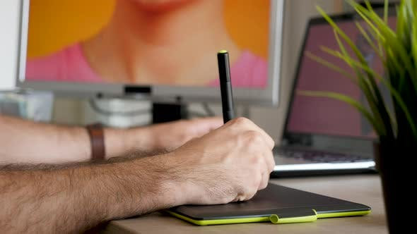 Man Holds a Pen and Works with a Digital Tablet