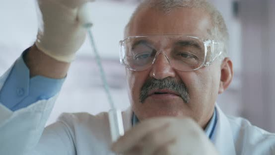 Thumbnail for Rack Focused Shot of Male Caucasian Scientist in Medical Gown and Goggles Pouring Red Liquid Into
