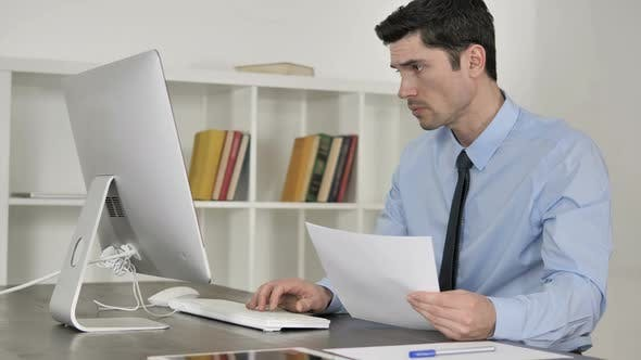 Thumbnail for Businessman Reading Documents and Working On Computer