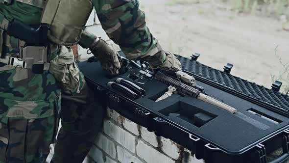 The Soldier Pulls a Rifle Out of the Ammunition Case and Insert Ammunition Clip Into Assault Rifle