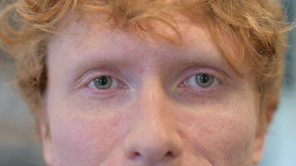 Close Up of Blinking Eyes of Young Redhead Man