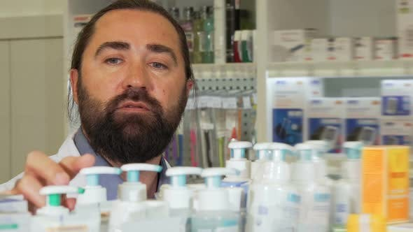 Thumbnail for Bearded Pharmacist Smiling To the Camera, While Working at Drugstore