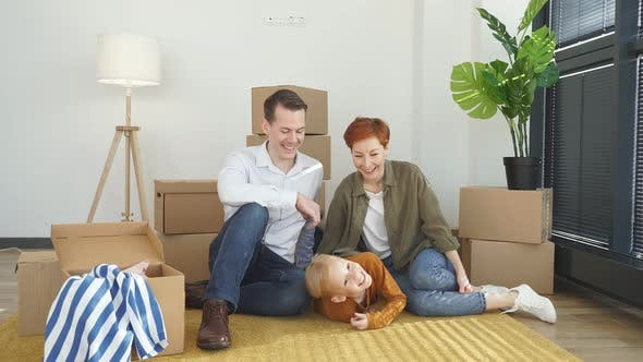 Young Family with Little Child Sit on Warm Floor Relaxing Together in Own Apartment Overjoyed Family