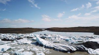 Aerial drone flight over Glacier Lagoon with icebergs.
