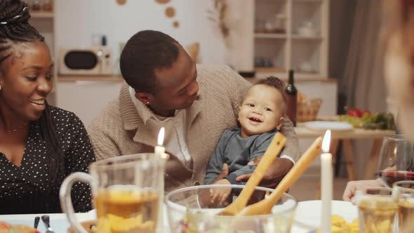 Thumbnail for Loving Afro-American Dad Sitting with Baby Son at Dinner Table with Friends
