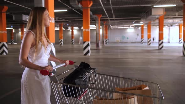 Thumbnail for Pretty Woman Carrying Shopping Cart in Parking