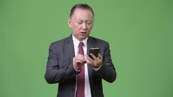 Thumbnail for Mature Japanese Businessman Using Phone