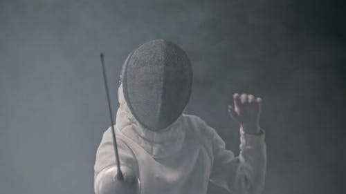 Fencing Training in the Studio - Young Woman Fencing in the Smoke