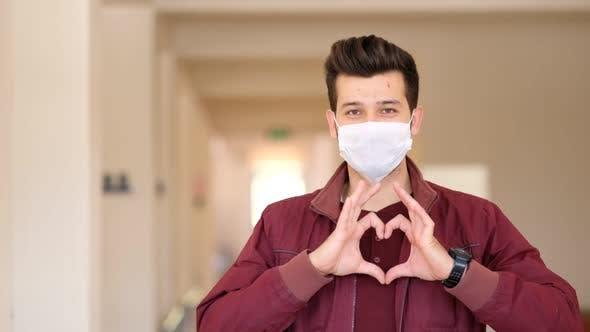 Happy doctor in protective mask on face gesturing heart symbol by hands.
