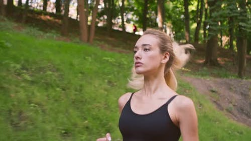 Motivated Young Female Runner Training in Park