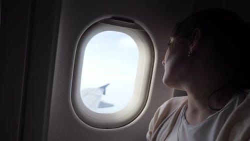 Portrait of Sleepy Tired Woman is Looking at Airplane Window Dirung Flight
