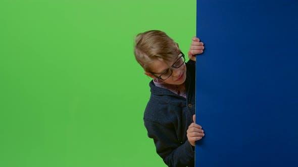 Thumbnail for Kind Boy erscheint von der Seite des Brettes halten Ihre Hände vor auf einem grünen Bildschirm
