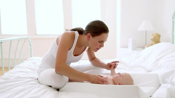 Thumbnail for Mother with baby on changing mat on bed