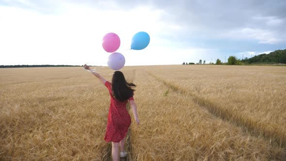 Happy Girl in Red Dress Running Through Golden Wheat Field with Balloons in Hand at Overcast Day