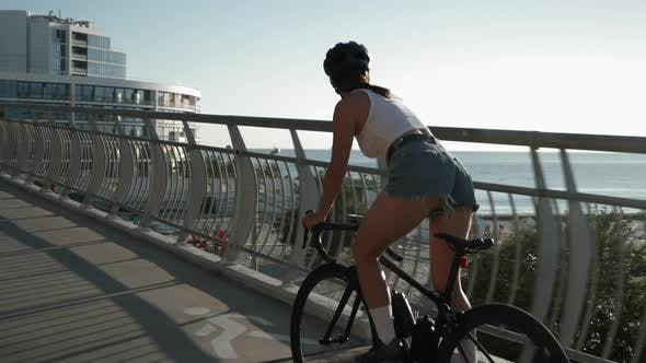 Thumbnail for Young stylish girl in helmet and casual clothes is cycling on bicycle on bridge at beautiful sunrise