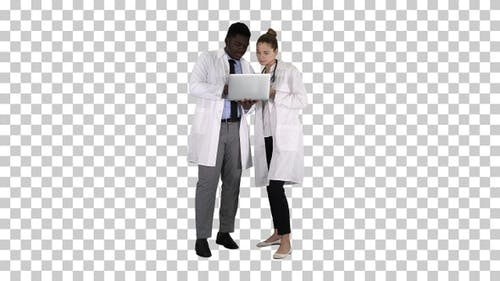 Medical staff working in front of a grey laptop while standing