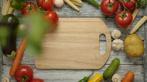 Thumbnail for Parsley Leaves Falling on a Cutting Board with Organic Vegetables Around