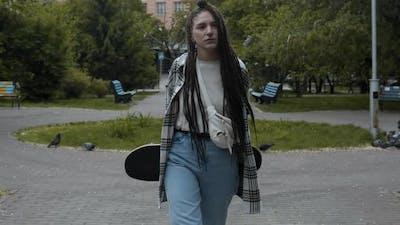 Girl skateboarder walking outdoors