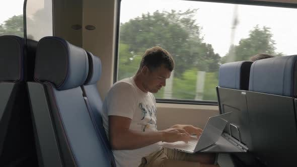 Man Using Laptop During Ride in Commuter Train