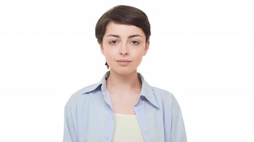 Young Brunette Caucasian Girl with Short Hairstyle Looking Calmly at Camera and Smiling
