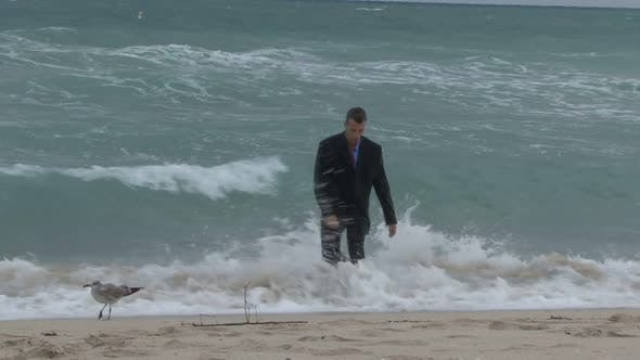 Male walking out of the ocean in suit with his head down