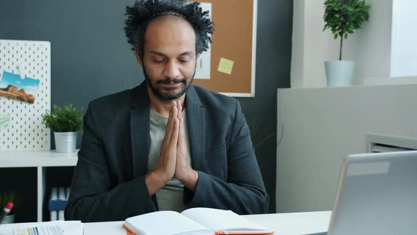 Middleaged Arab Man Holding Hands in Namaste and Looking at Notebook Sitting at Desk in Office