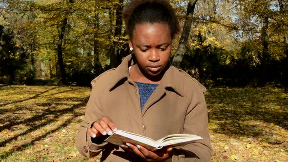 Thumbnail for Young African Happy Girl Stands in the Woods, Observes Landscape and with Interest Reads a Book