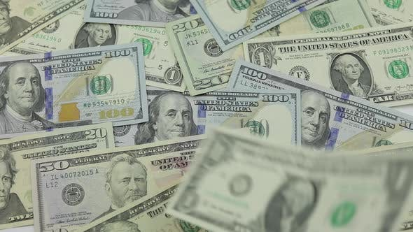 Thumbnail for Dollar Bills Fall on the Table with American Dollars of Different Denominations