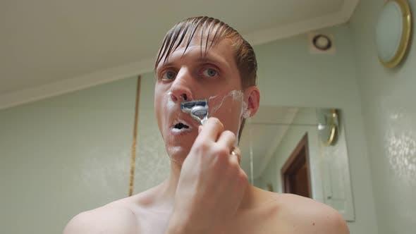 Man Shaving With A Razor