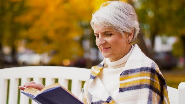 Thumbnail for Happy Senior Woman Reading Book at Autumn Park 30