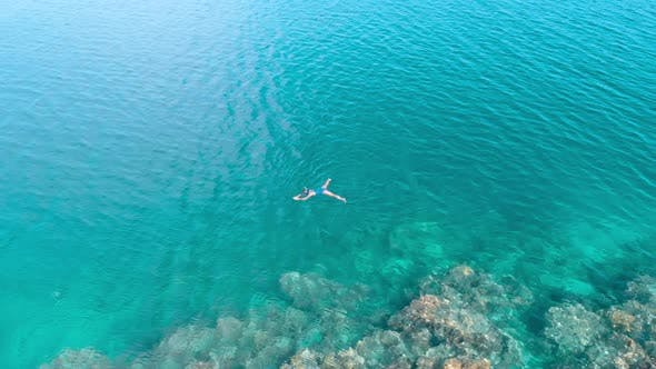 Thumbnail for Aerial slow motion: woman snorkeling on coral reef tropical sea from above