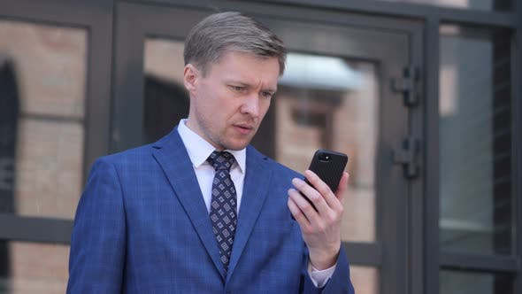 Wondering Businessman in Shock while using Smartphone