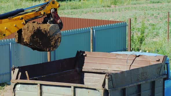 Cover Image for Top View of Excavator Bucket Pours Ground Into the Truck