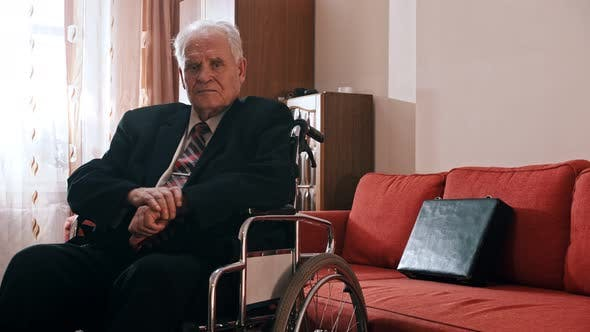 Thumbnail for Elderly Grandfather - Sad Grandfather Is Sitting in a Wheelchair in His Room and Looking at the