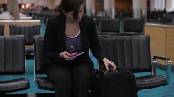 Thumbnail for Woman waits in airport lobby