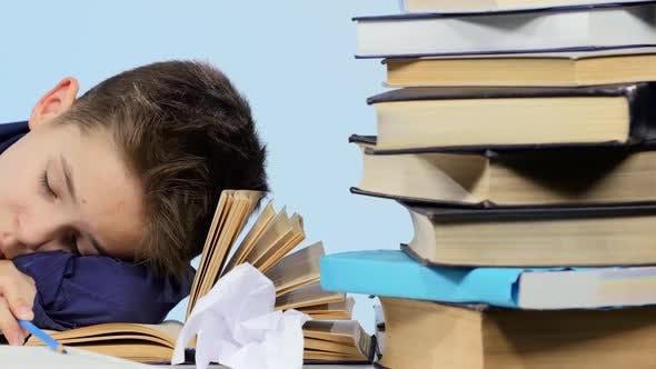 Tired Boy Fell Asleep at a Desk Between Books. Blue Background
