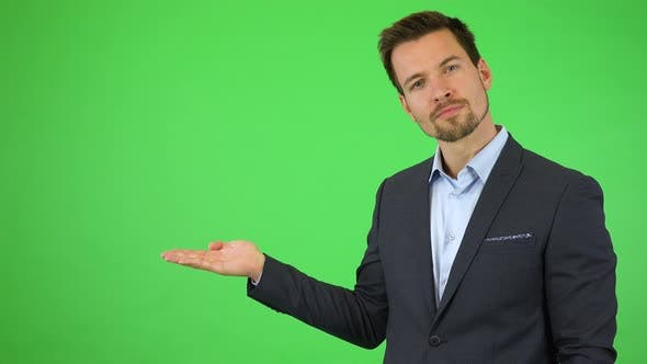 Thumbnail for A Young Handsome Businessman Puts Out a Hand with a Product, Smiles and Nods - Green Screen Studio