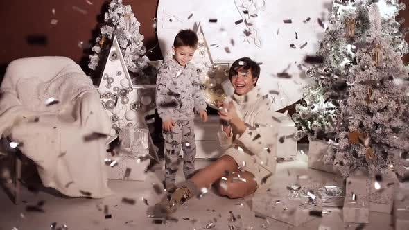 Thumbnail for Playful Kid in Pyjamas and His Mother Under Confetti