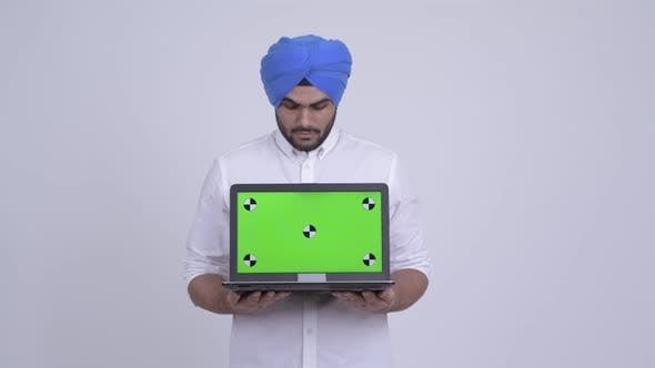 Thumbnail for Happy Young Bearded Indian Sikh Man Showing Laptop