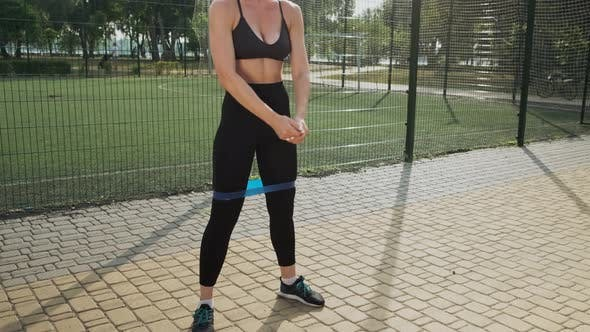 Woman Exercising Squats with Elastic Band Outdoors in Summer
